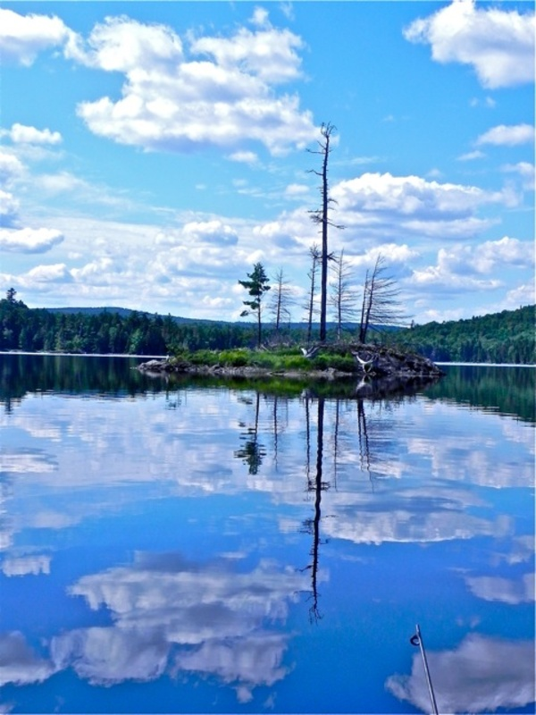 The water mirrors the sky and small islands abound on a perfect day for canoeing in Maine.