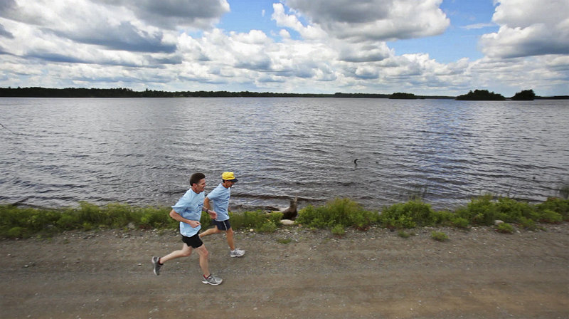 Early last month, Bob Bryant, left, and Dale Lolar run past the Grand Falls Flowage created by a dam on the St. Croix River. The two were participating in a 100-mile sacred run relay organized by members of the Passamaquoddy Tribe to bring attention to the plight of alewives, which have been prevented from reaching their spawning habitat because fishways had been closed along the river.