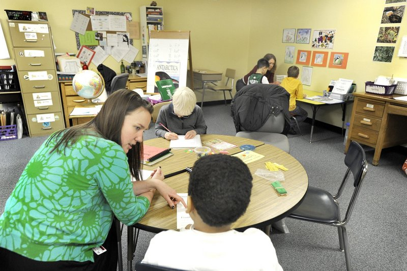 A teacher's aide works with a student at Longfellow Elementary School in Portland. The opening of charter schools in Maine will siphon money from public schools, a reader says.
