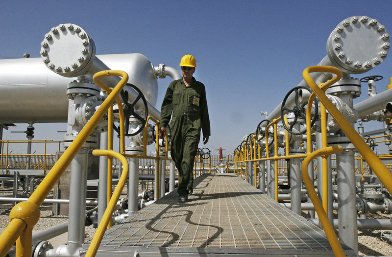 """Iranian oil technician Majid Afshari makes his way to the oil separator facilities in the Azadegan oil field southwest of Tehran in 2008. Iran says it has stored imported goods and hard currency for a """"battle"""" against EU sanctions."""