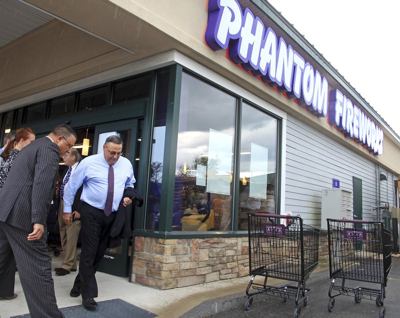 Gov. Paul LePage dashes for his car in a downpour Monday following a tour and news conference at Phantom Fireworks in Scarborough, a store that opened last month.