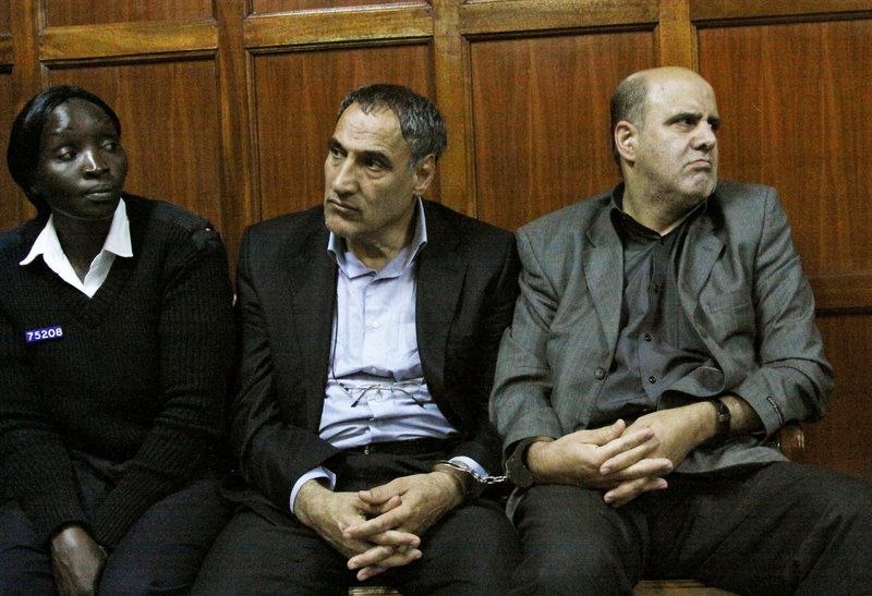 A Kenyan police officer, left, accompanies Iranian nationals Sayed Mansour Mousavi, center, and Ahmad Abolfathi Mohammad last week in the Nairobi magistrates court, where they faced charges related to the possession of explosives.