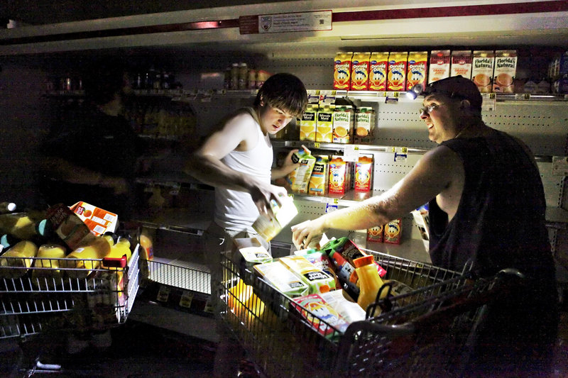 David Robertson and Steve Jones fill their shopping cart with juice Monday at the darkened Mick-or-Mack IGA grocery store in New Castle, Va. Supermarkets around the region struggled to keep groceries from going bad.