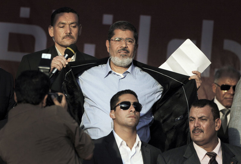 Egyptian President-elect Mohammed Morsi opens his jacket Friday to show his supporters that he is not wearing a bullet-proof vest.