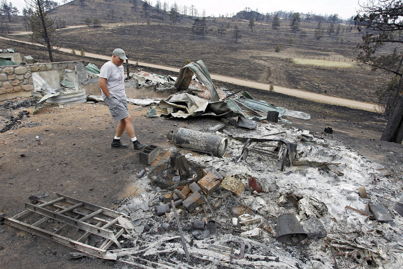 Martin Jiles looks over the ashes of his home that was destroyed by the High Park Fire near Livermore, Colo., on Monday. Residents have been allowed to return home as crews fully contained the 136-square-mile wildfire, which killed one resident and destroyed 259 houses.