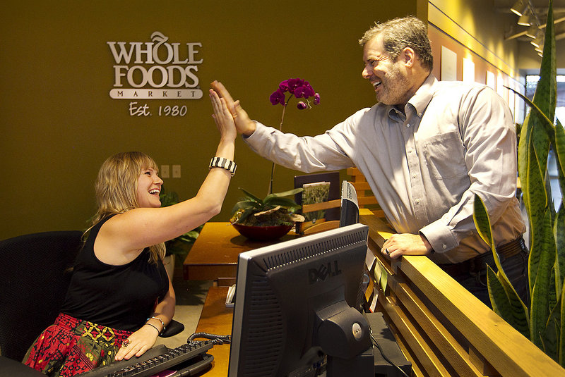 Mark Ehrnstein, global vice president for team member services at Whole Foods, and receptionist Nikki Newman greet one another at their Austin, Texas, offices. Whole Foods caps executive pay at 19 times that of the lowest-paid employee.