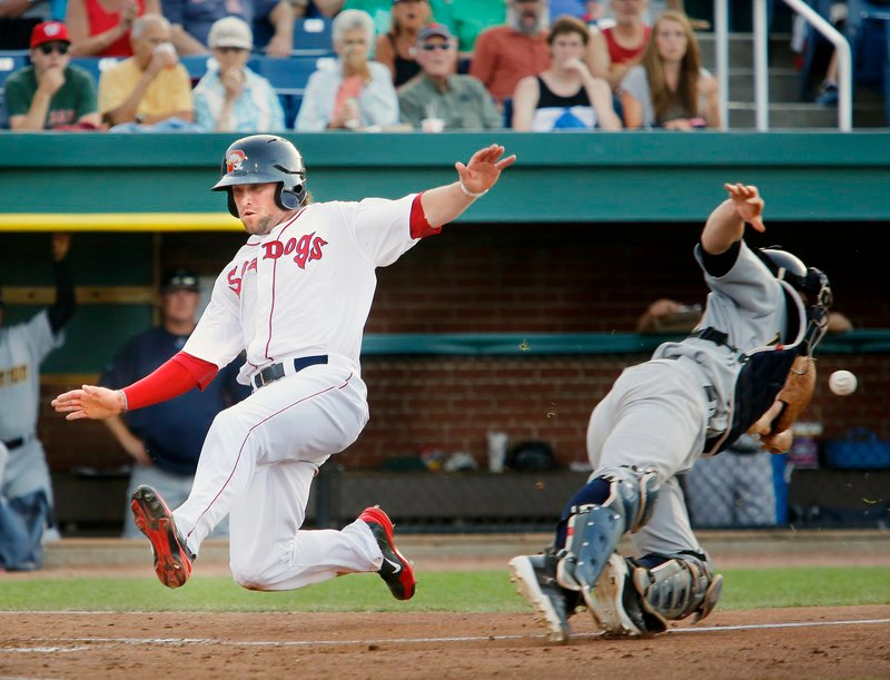 Bryce Brentz of the Portland Sea Dogs slides in to score Tuesday night as Trenton catcher Jeff Farnham lunges for the throw during the fourth inning at Hadlock Field. Trenton earned an 11-3 victory against the Sea Dogs, who will start a series tonight at New Hampshire.