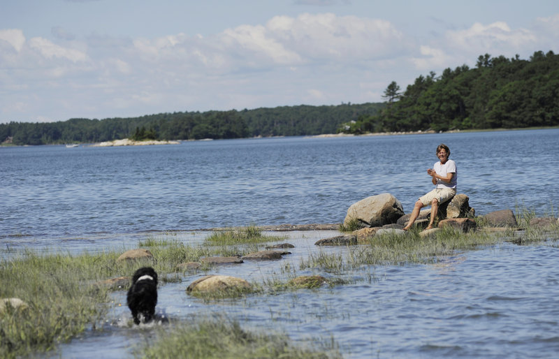 Linda Fraser-Campbell calls for her dog, Lady, to join her on some rocks along the shore at Middle Bay Cove at the end of a trail at Skolfield Shores Preserve in Harpswell. Fraser-Campbell, who lives near the property, says she hikes the trails twice a day.