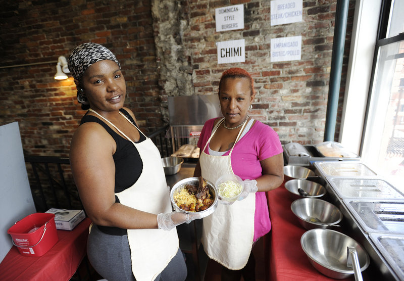 Aidalina Costoso, left, and Lourdes Suero of La Cocina Dominicana show off the barbecue beef ribs with rice and peas, sweet plantains and cabbage salad during a recent lunch hour. The eatery opened for business a few weeks ago.
