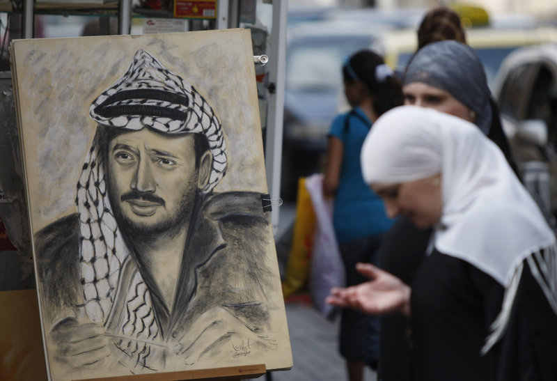 A drawing of the late Palestinian leader Yasser Arafat is displayed on a street corner in the West Bank city of Ramallah on Thursday. Palestinian leaders want more information before deciding on digging up Arafat's body.