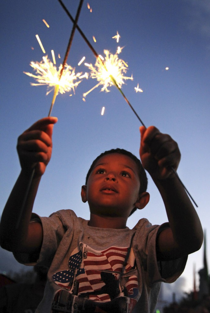 Quin Lucas, 4, in Portland on vacation from Pennsylvania, lights up the night with sparklers while waiting for the fireworks with his parents, Heather and Quasar, at the Eastern Prom in Portland on Thursday.