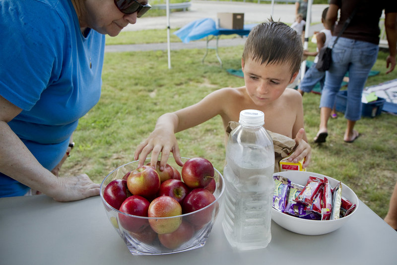 Matthew Keene, 6, of Windham chooses an apple at the free lunch at Little Falls Landing on Friday.