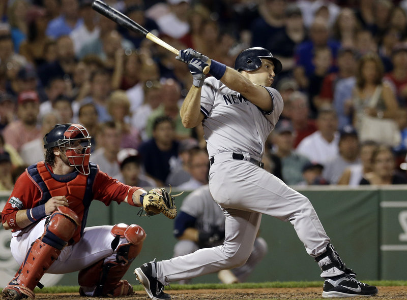 Mark Teixeira of the New York Yankees follows through on a two-run triple in the seventh inning Friday night as Red Sox catcher Jarrod Saltalamacchia watches. The triple was the key hit in the Yankees' 10-8 victory.