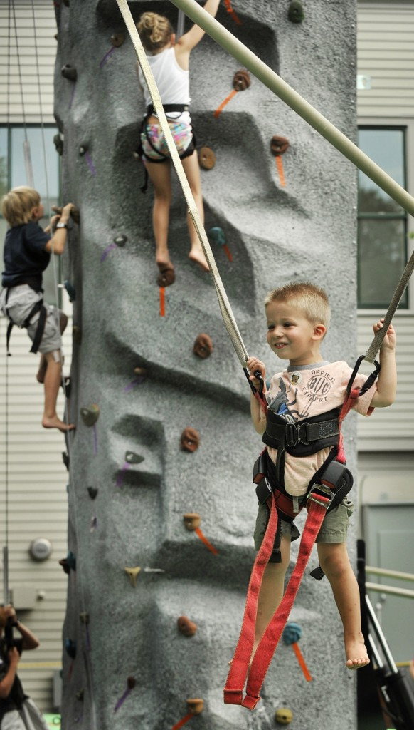 Ryan Phelan, 3, who was visiting with his family from Albany, N.Y., plays on a jumper while other kids climb on a rock wall behind him in Freeport.