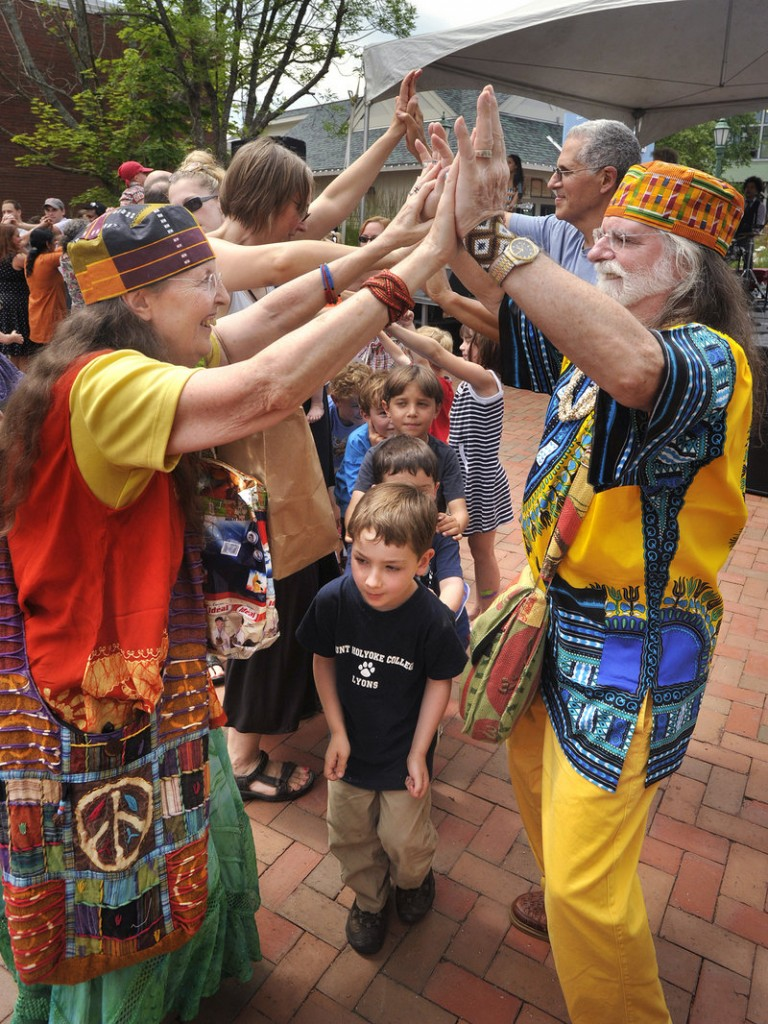 Dorothy and Paul Fortin of Brunswick, in festive dress, help make a tunnel for kids to dance through during a performance by the Dan Zanes Band.