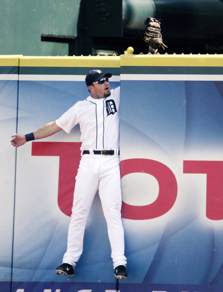 Ryan Raburn of the Tigers gets stuck in the gate after making a leaping attempt on a home run hit by Kansas City's Mike Moustakas Saturday night.
