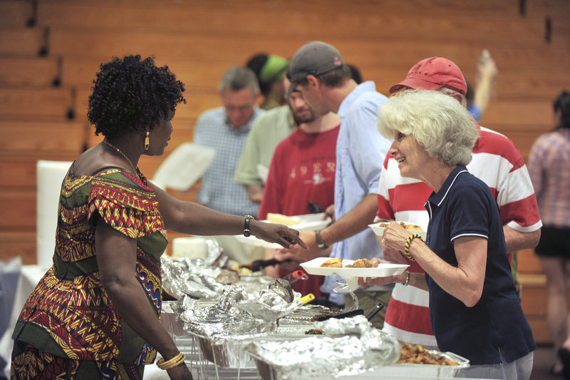 Mary Ben, left, suggests Sudanese food choices to Donna and Brian Gordon of Scarborough, as they make their way down the buffet line at the Southern Maine Community College gymnasium Saturday.