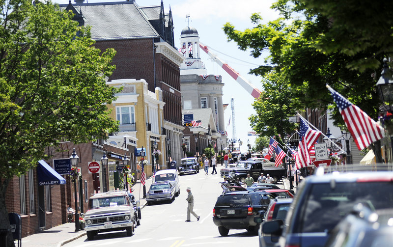 Antique cars draw visitors to Front Street in Bath, which was closed to traffic on Sunday, for the last of five days of Bath Heritage Days. A Bath Iron Works crane towers in the background.