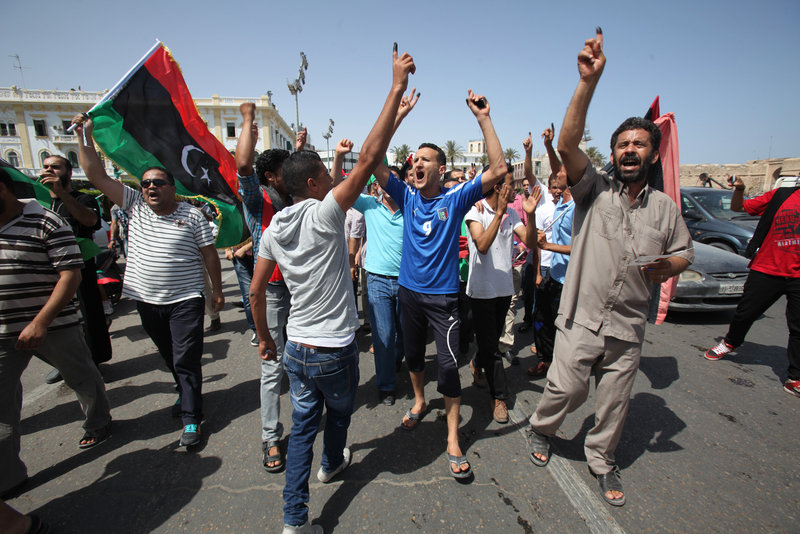 Libyans in Tripoli hold up ink-marked fingers to show they have voted as they celebrate in Martyrs' Square on Saturday. Observers say Libya, unlike Egypt and Tunisia, could pose a setback to the Muslim Brotherhood by supporting non-Islamist candidates.