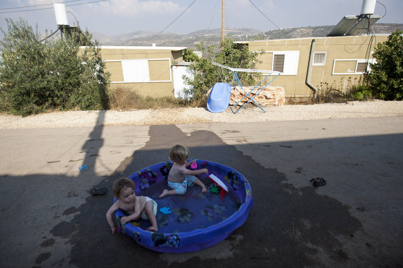 Children of Jewish settlers play in a pool at the unauthorized West Bank outpost of Nofei Nehemya on Monday. A government-appointed committee is recommending that Israel legalize dozens of unauthorized West Bank settlement outposts.