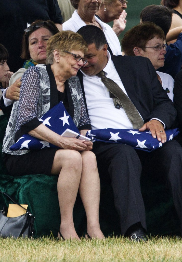 Barbara Annechino is comforted by her brother Jeffrey Christiano during the burial service for their father, Air Force Col. Joseph Christiano of Rochester, N.Y., and five others Monday at Arlington National Cemetery.
