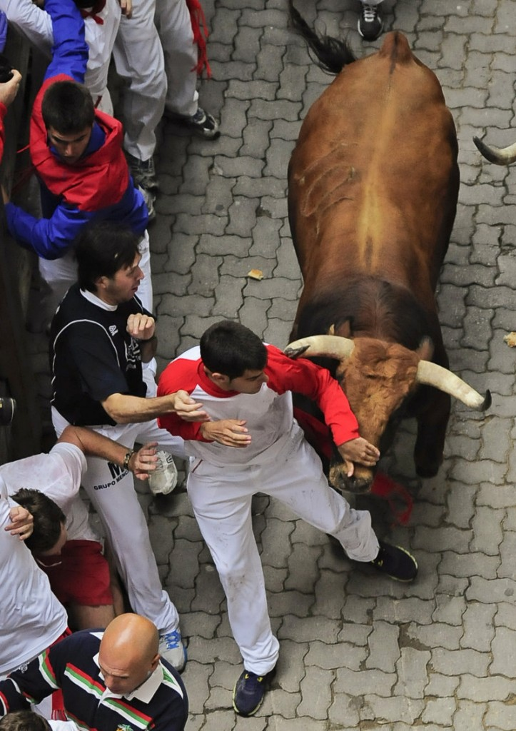 Revelers get out of the way of a bull during the third day of the running of the bulls at the San Fermin festival in Pamplona, Spain, on Monday.