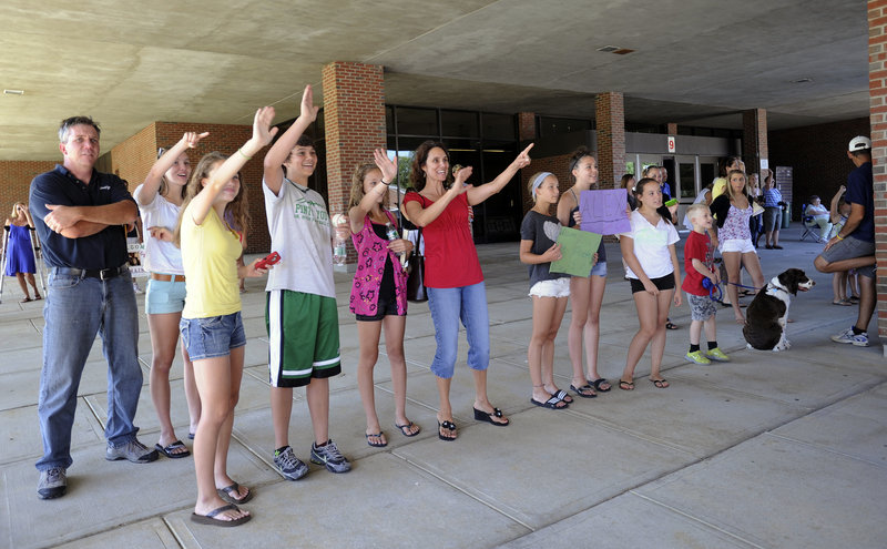 Fresh Air Fund host families wave to their visitors as they arrive on a bus at Kennebunk High School on Tuesday.
