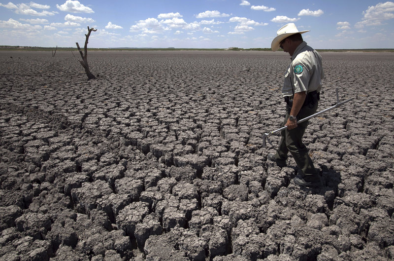 Texas State Park police Officer Thomas Bigham walks across the cracked lake bed of O.C. Fisher Lake in San Angelo during 2011's heat wave. Researchers calculate that global warming has made such a Texas heat wave about 20 times more likely during a La Nina year.