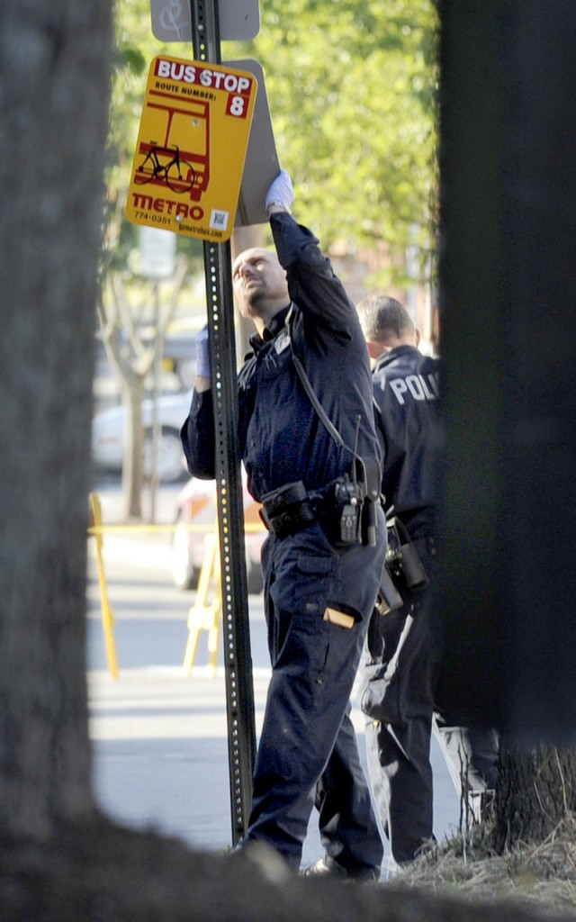 A Portland police officer looks for evidence on a sign post near 105-107 India St. after an early morning shooting Wednesday. Witnesses told police that a loud argument erupted, then several shots were fired.
