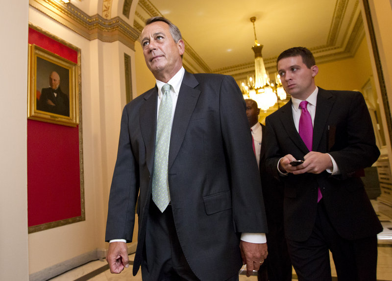 House Speaker John Boehner of Ohio, left, leaves the House chamber Wednesday after the Republican-controlled House voted 244-185 to repeal Obama's health care law.