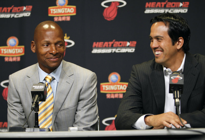 Ray Allen, who left the Celtics after five years to play with the Heat, sits next to Coach Erik Spoelstra during Wednesday's press conference in Miami. Allen said he will find a way to fit in with the NBA champions.