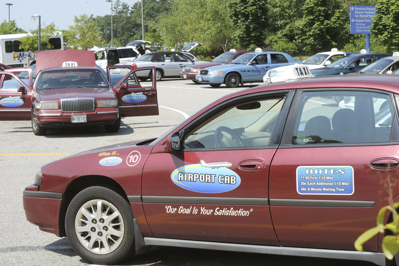 Taxis wait their turn in a parking lot to pick up fares at the Portland International Jetport on Friday.