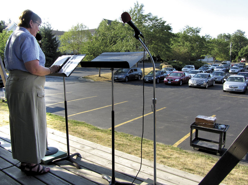 Naomi Garber, pastor of First Lutheran Church, preaches to her congregation by way of their car radios during a typical summer drive-in service in the church's parking lot last week in Janesville, Wis.