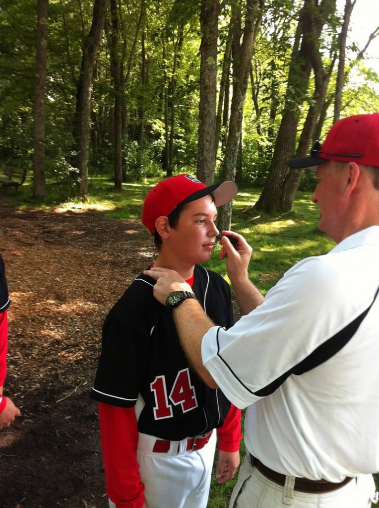 Scarborough Manager Neal Pratt applies eye black to catcher Owen Garrard before a game in South Portland. The team calls itself Eye Black because they all play with black triangles under their eyes, imitating the style of major league baseball star Bryce Harper.