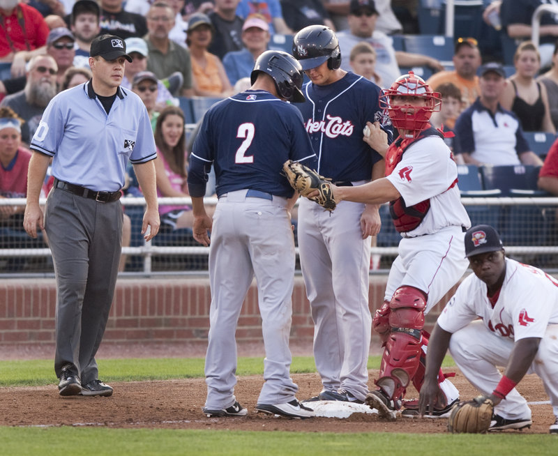 Sea Dogs catcher Dan Butler tags Ryan Goins, left, and Jake Marisnick of the Fisher Cats after both runners ended up on third base following a rundown. Marisnick was out initially, and Goins also was called out because of coach's interference after he left the base.