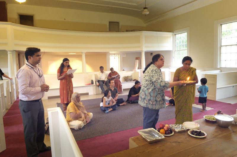 Worshippers pray at the new Hindu temple on the Scarborough-Buxton town line Thursday. The group is still renovating the building and the temple will officially open in the fall. Sandeep Gandra, at left, will serve on the board of directors.