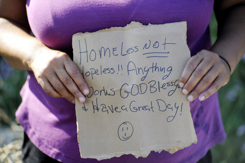 """Kelly Noble holds a sign that says: """"Homeless, not hopeless!! Anything works. God bless you and have a great day!"""" while panhandling in Portland."""