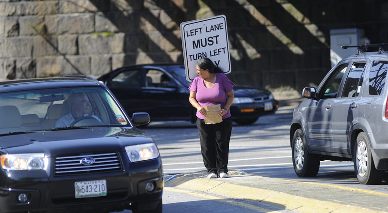 Kelly Noble of Portland panhandles from the median strip at St. John Street and Park Avenue in Portland on Thursday. A proposed ordinance that would prohibit panhandlers from standing in the median will go before the Portland City Council today.