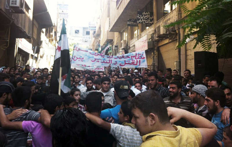"""In this citizen journalism image taken Friday, Syrians chant slogans at a Damascus rally. Partially translated, the banner reads: """"A horrible regime, killing and destruction."""" A government assault on the village of Tremseh reportedly killed as many as 150 people."""
