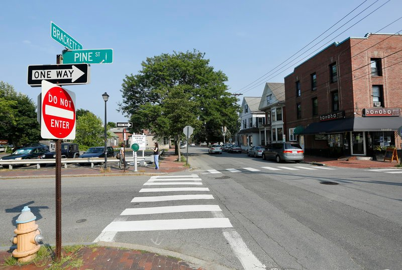 A crosswalk leads to the site at the corner of Pine and Brackett streets where a developer would put 39 market-rate apartments. Two old buildings would have to come down.