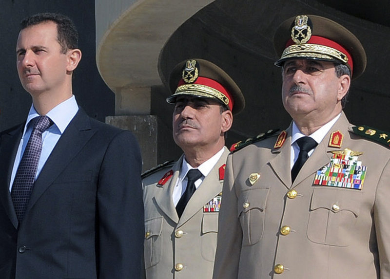 Syrian President Bashar Assad, left, is seen in 2011 with Defense Minister Gen. Dawoud Rajha, right. Rajha was killed Wednesday in a suicide blast inside the National Security building in Damascus, during a meeting of Cabinet ministers.