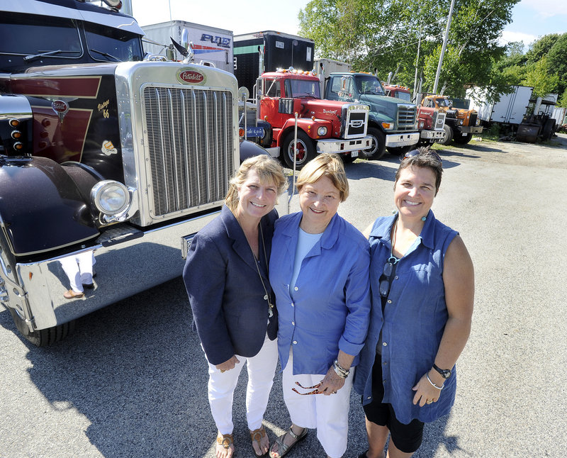 From left, Erv Bickford's daughter Tamson Bickford-Hamrock, his wife, Lyn Bickford, and daughter Susan Bickford stand in front of some of his trucks. The family hopes to complete the pavilion by next July, in time for the Yarmouth Clam Festival that Erv Bickford loved.