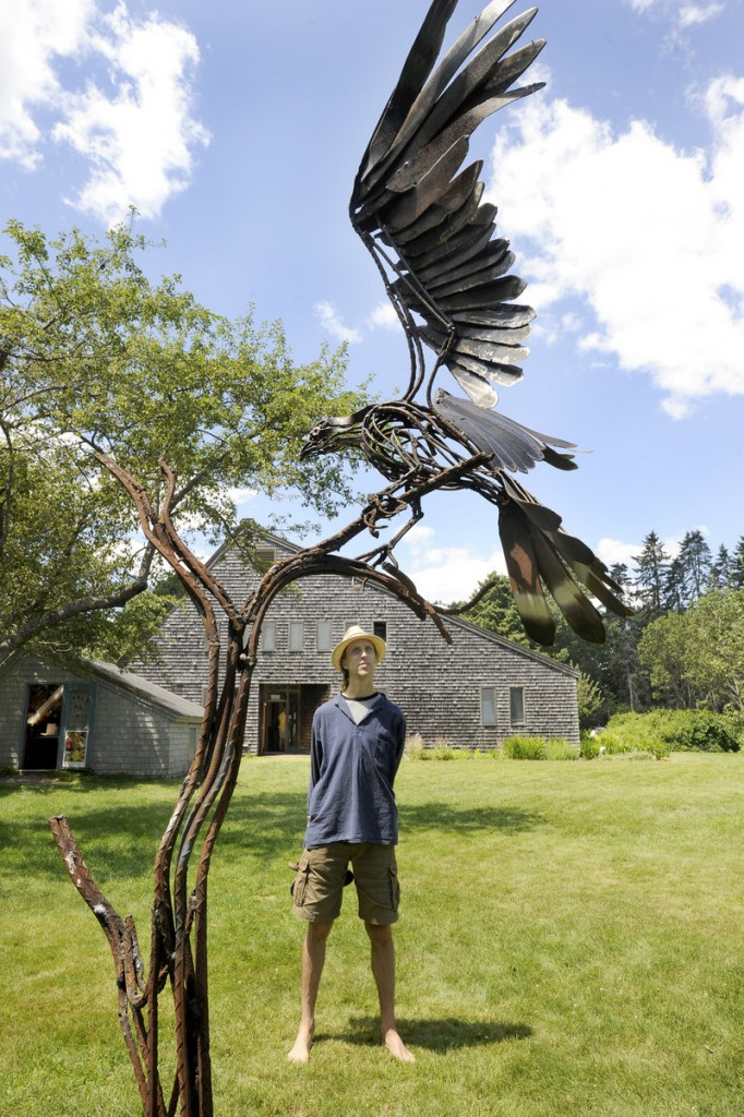 """David Yearwood of Portland checks out """"Osprey"""" by Wendy Klemperer, among the """"On the Wing"""" sculptures on view at Maine Audubon in Falmouth and at Coastal Maine Botanical Gardens in Boothbay through Sept. 30."""