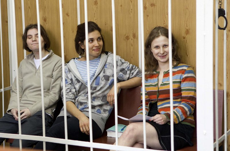 Yekaterina Samutsevich, from left, Nadezhda Tolokonnikova and Maria Alekhina, members of a feminist rock band, attend a preliminary hearing in a Moscow courtroom Friday. They have been held for more than four months so far.