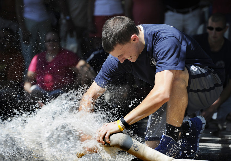 Tyler Woods, a member of the Yarmouth Fire and Rescue team, competes in the Firefighters Muster at the Yarmouth Clam Festival on Saturday.