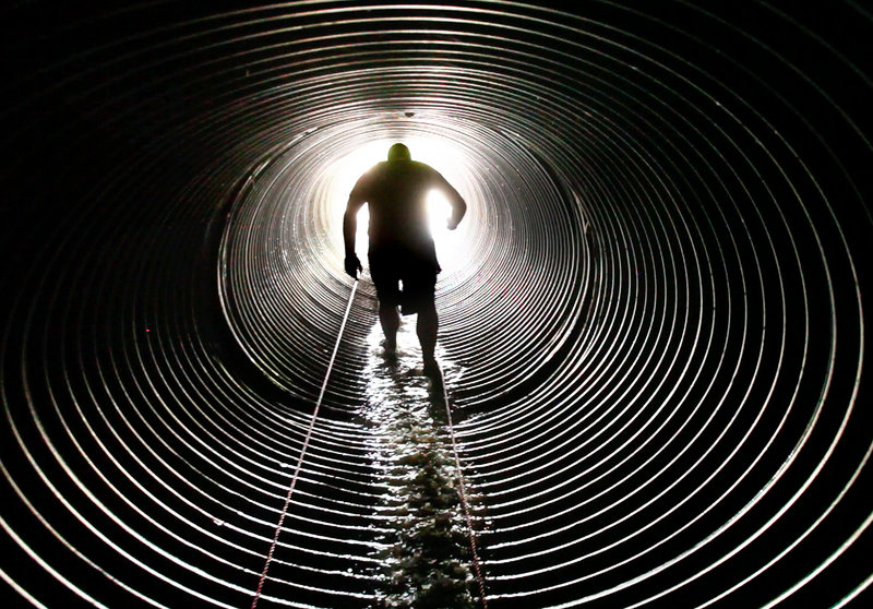A competitor makes his way through a culvert dubbed the Hole of Horror while competing in the Tough Mountain Challenge at Sunday River in Newry on Saturday. This year's field was capped at 2,500 competitors – 1,500 more than last year.