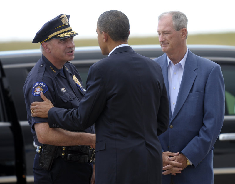 President Obama greets Aurora Police Chief Daniel Oates as Mayor Steve Hogan, right, watches after the president's arrival at Buckley Air Force Base in Colorado on Sunday.