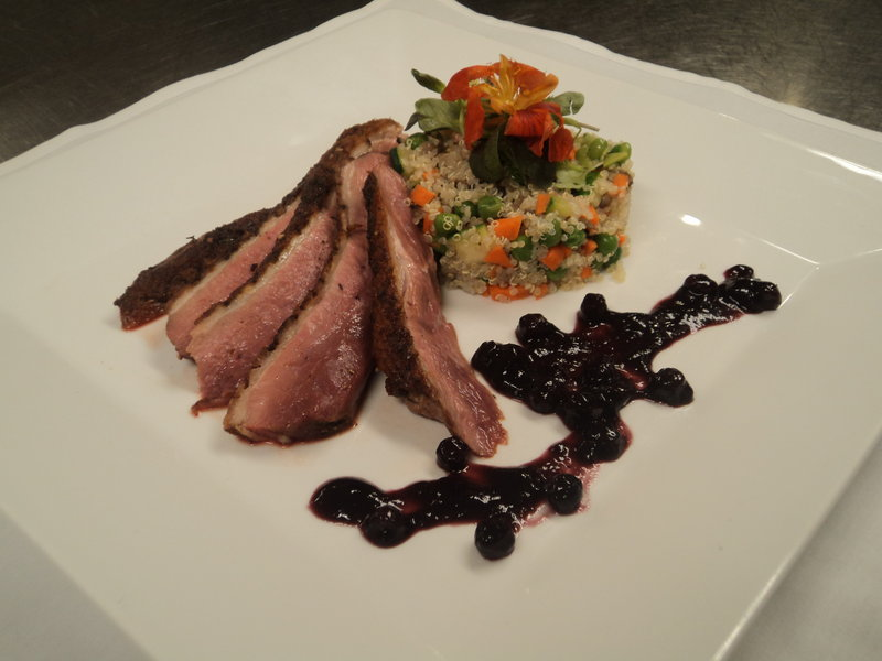 Spice-rubbed pan-seared duck breast with organic farmed vegetables, quinoa and blueberry-red wine sauce is offered by Mitchell Kaldrovich, chef at the Sea Glass Restaurant at Inn by the Sea in Cape Elizabeth.