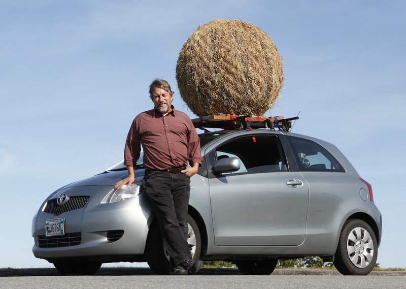 Portland artist Michael Shaughnessy and the Hay Ball, mounted atop his car. Shaughnessy has a Facebook page for the artwork, and invites photographs of it.