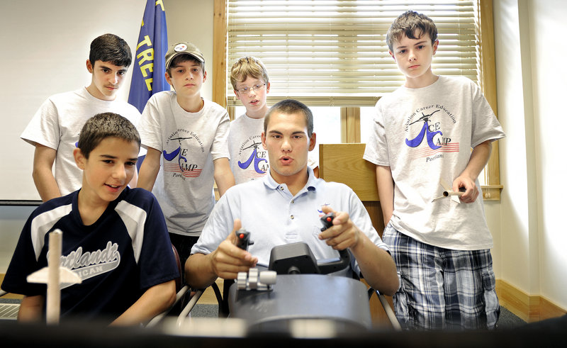 Levi Swan, 19, of Caribou, a maintenance crew chief with the Air National Guard, demonstrates a flight simulator for campers Thursday at the Aviation Career Education camp at the Boy Scouts' conference facility near the Portland Jetport.